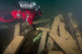 Parks Canada underwater archaeologist Filippo Ronca measures the diameter of a cannon found with the wreckage of the HMS Erebus. Photo by Thierry Boyer, Parks Canada.