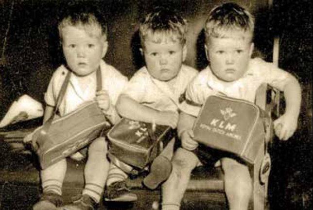 The triplets on their way to Canada with their KLM tote bags.