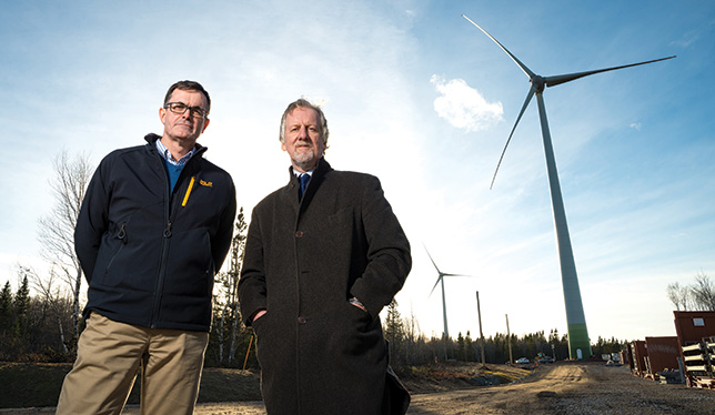 The wind turbines rise up behind Donnie MacIsaac, director of facilities management at CBU, and president David Wheeler. Photo courtesy of Cape Breton University.